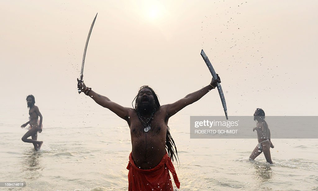 An Indian Hindu Sadhu or holy man shouts while holding a sword after he and others like him ran into the waters of the Sangham or the confluence of the the Yamuna and Ganges rivers during the Kumbh Mela in Allahabad on January 14, 2013. Hundreds of thousands of Hindu pilgrims led by naked, ash-covered holy men streamed into the sacred river Ganges at the start of the world's biggest religious festival. The Kumbh Mela in the Indian town of Allahabad will see up to 100 million worshippers gather over the next 55 days to take a ritual bath in the holy waters, believed to cleanse sins and bestow blessings.