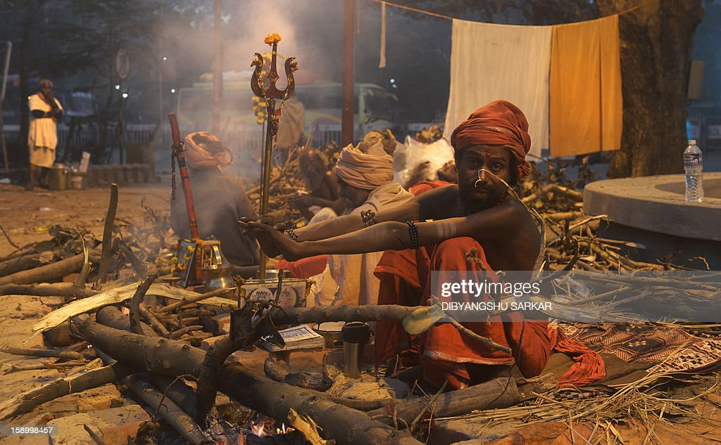 An Indian Hindu Sadhu or holy man warms himself near a fire at a make-shift camp in Kolkata on January 5, 2013. Sadhus form all over the country started to gather in Kolkata on their way to the annual Hindu holy festival Gangasagar Mela, more that hundred thousand Hindu pilgrims will gather at the Gangasagar to take a dip in the ocean at the confluence of the River Ganges and the Bay of Bengal, on the occasion of Makar Sankranti, a holy day of the Hindu calendar considered to be of great religious significance in Hindu mythology. AFP PHOTO/ Dibyangshu SARKAR