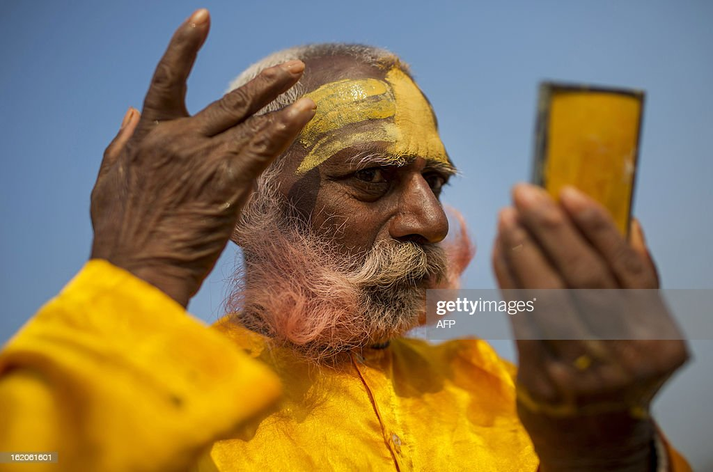 An Indian Hindu Sadhu paints his forehead after bathing at the Sangam or confluence of the Yamuna, Ganges and mythical Saraswati rivers at the Kumbh Mela in Allahabad on February 19, 2013. The Kumbh Mela in the town of Allahabad will see up to 100 million worshippers gather over 55 days to take a ritual bath in the holy waters, believed to cleanse sins and bestow blessings. AFP PHOTO/ Andrew Caballero-Reynolds