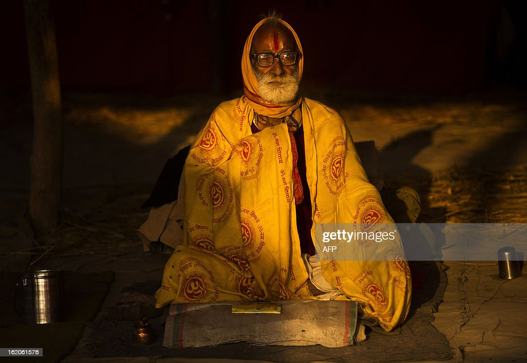 An Indian Hindu sadhu prays in his tent near the Sangam or confluence of the Yamuna, Ganges and mythical Saraswati rivers at the Kumbh Mela in Allahabad on February 19, 2013. The Kumbh Mela in the town of Allahabad will see up to 100 million worshippers gather over 55 days to take a ritual bath in the holy waters, believed to cleanse sins and bestow blessings. AFP PHOTO/ Andrew Caballero-Reynolds