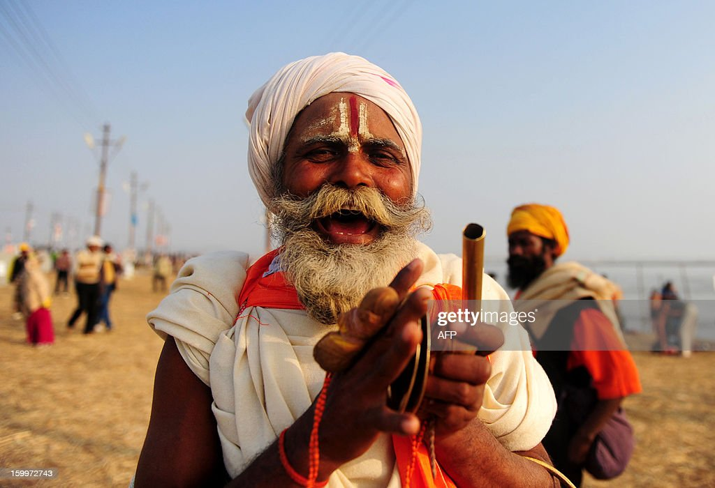 An Indian Hindu sadhu sings a religious song after taking a dip in the Sangam, the confluence of the rivers Ganges and Yamuna in Allahabad on January 24, 2013. The Kumbh Mela in the Indian town of Allahabad will see up to 100 million worshippers gather over the next 55 days to take a ritual bath in the holy waters, believed to cleanse sins and bestow blessings. AFP PHOTO/ Sanjay KANOJIA