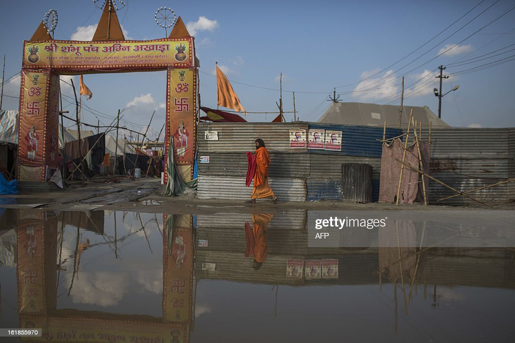 An Indian Hindu sadhu walks into an encampment next to a flooded area at the Kumbh Mela in Allahabad on February 17, 2013. The Kumbh Mela in the town of Allahabad will see up to 100 million worshippers gather over 55 days to take a ritual bath in the holy waters, believed to cleanse sins and bestow blessings. The Kumbh Mela, which ends in March, takes place every 12 years in Allahabad. AFP PHOTO / Andrew Caballero-Reynolds
