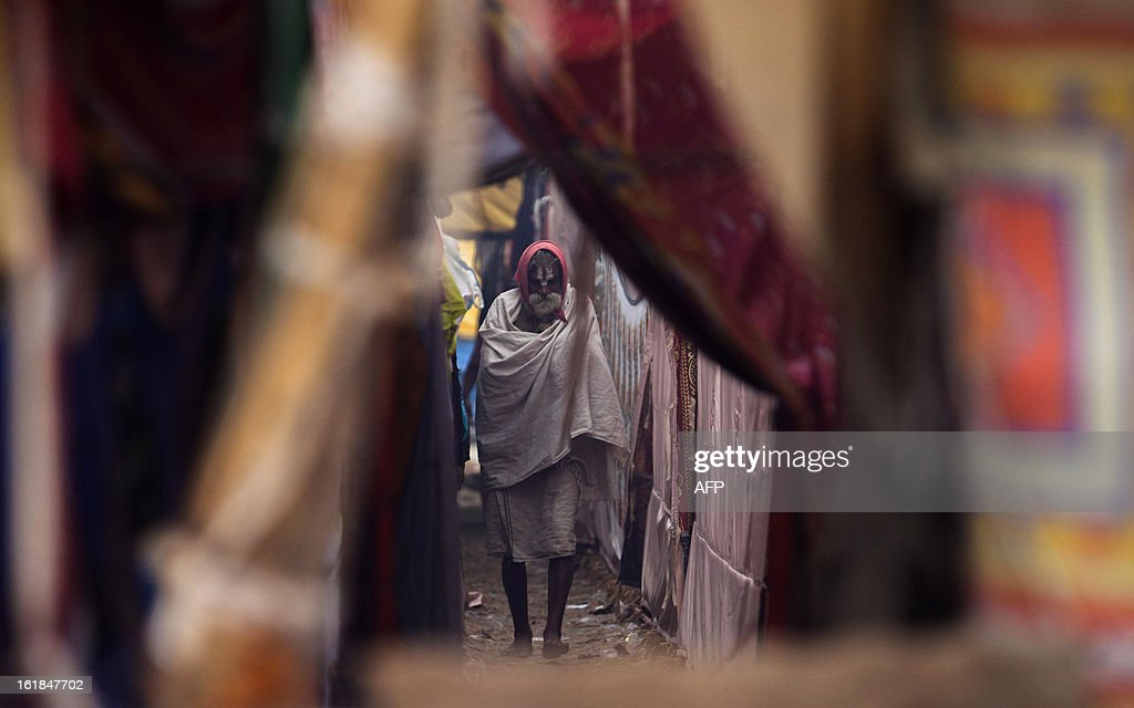 An Indian Hindu Sadhu walks past a row of tents at the Kumbh Mela in Allahabad on February 17, 2013. The Kumbh Mela in the town of Allahabad will see up to 100 million worshippers gather over 55 days to take a ritual bath in the holy waters, believed to cleanse sins and bestow blessings. AFP PHOTO/ Andrew Caballero-Reynolds