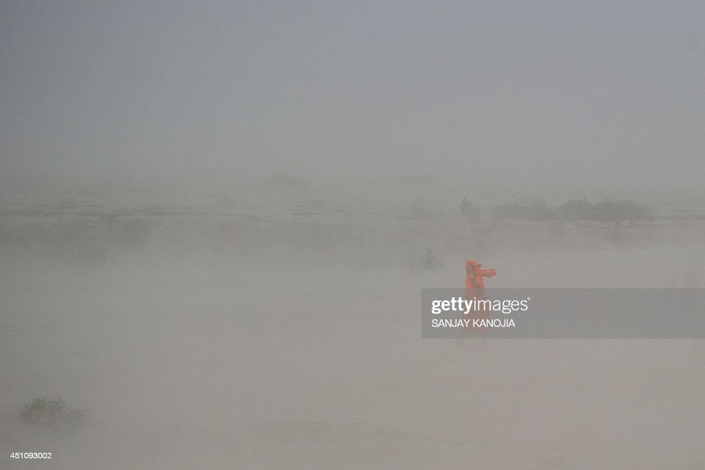 An Indian Hindu sadhu (holy man) walks through a dust storm at the Sangam, the confluence of the rivers Ganges, Yamuna and mythical Saraswati, in Allahabad on June 23, 2014.