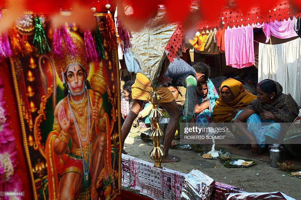 An Indian Hindu volunteer serves meals to female devotees near a figure of Hindu God Lord Hanuman (L) at one of the hundreds of camps set up by different Hindu religious groups during the Maha Kumbh Mela festival in Allahabad on February 8, 2013. The Kumbh Mela in the town of Allahabad will see up to 100 million worshippers gather over 55 days to take a ritual bath in the holy waters, believed to cleanse sins and bestow blessings.