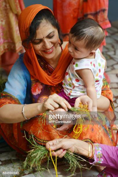 An Indian Hindu woman holds her son as she offers a ritual prayer during the traditional 'Gai Bachra Puja ' at a temple in Amritsar on August 18 2017...