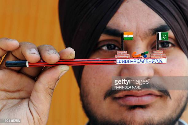 An Indian hockey fan displays a wooden pencil decorated with miniature Indian and Pakistani flags and a hockey stick in Amritsar on February 27 2010...