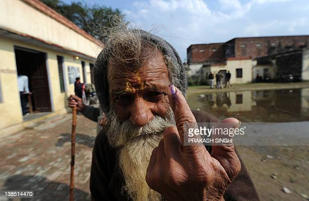 An Indian holy man shows his finger mark after casting his vote at a polling booth for the state assembly elections in Ayodhya in Uttar Pradesh on...