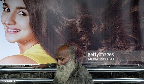 An Indian homeless man sleeps at a bus stop with an advertisement for hair products featuring Bollywood actress Alia Bhatt in Mumbai on June 16 2015...