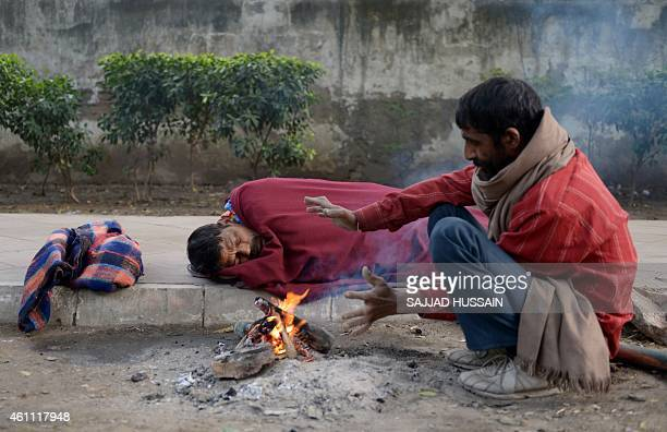 An Indian homeless man warms himself as another sleeps alongside a fire at the roadside in New Delhi on January 7 2015 Many poor and homeless...