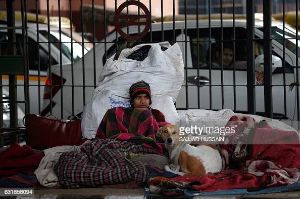 An Indian homeless man wrapped in a blanket sits on a footpath during a cold morning in New Delhi on January 17 2017 HUSSAIN