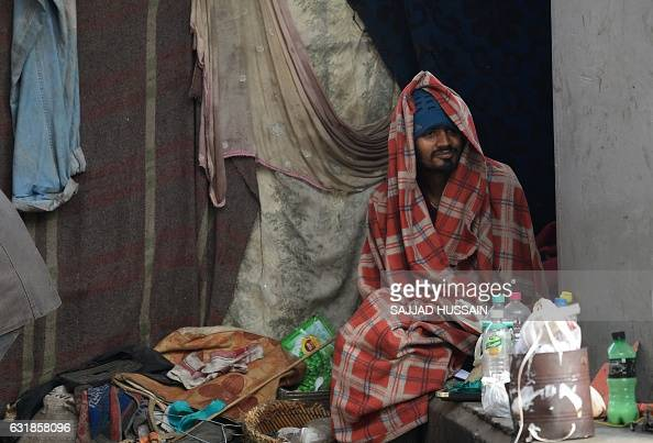 TOPSHOT An Indian homeless man wrapped in a blanket sits on a footpath during a cold morning in New Delhi on January 17 2017 HUSSAIN