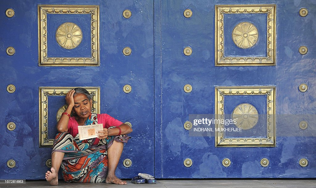 An Indian homeless woman reads a religious scripture sitting outside the closed doors of a bank in Mumbai on December 1, 2012. The city's civic body Brihanmumbai Municipal Corporation (BMC) will start a four new night shelters for the homeless in addition to the seven night shelters currently operational in the city by the end of December 2012. AFP PHOTO/INDRANIL MUKHERJEE