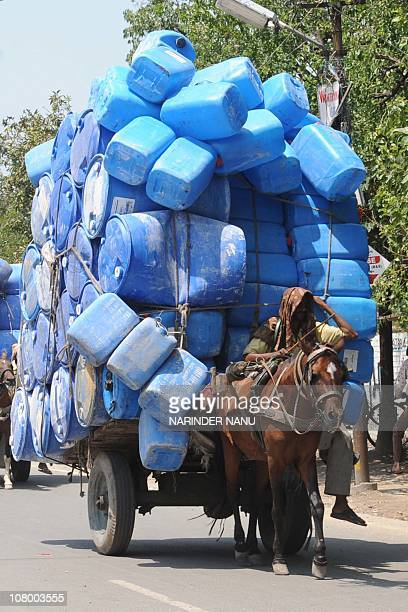 An Indian horse cart driver transports empty plastic containers in Amritsar on July 15 2009 This northwestern Indian city horse cart driver earns 150...
