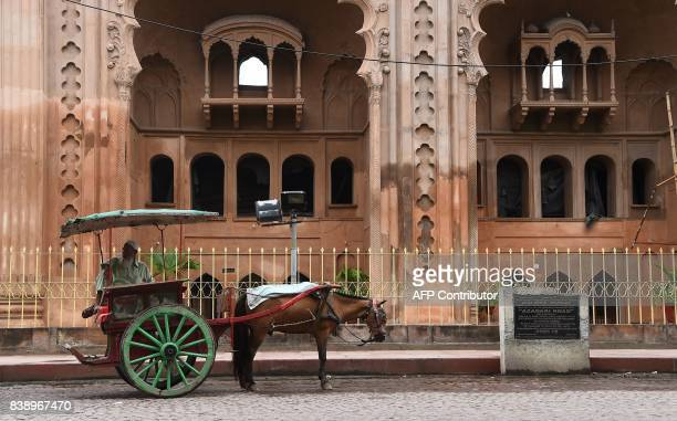 An Indian horse cart owner waits for passangers outside the Bara Imambara a colossal imambara in Lucknow northern India on August 25 2017 / AFP PHOTO...