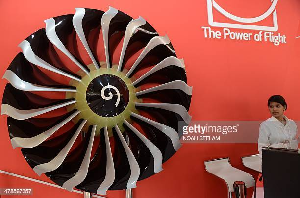 An Indian hostess stands beside the fan of a CFM 567BE engine whic is used in the Boeing 737 aircraft on display at an exhibitors venue at the India...