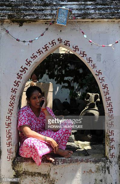 An Indian housewife speaks on her mobile phone as she sits outside her home in Mumbai on September 27 2011 India's telecom watchdog the Telecom...