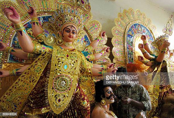An Indian idol maker is surrounded by semi finished idols of the tenarmed Hindu goddess Durga at a workshop in Bangalore 04 October 2005 The artist...