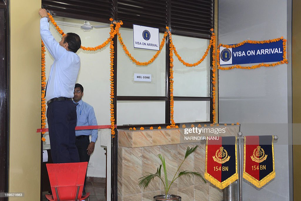 An Indian immigration employee decorates the 'visa on arrival' counter and a small office at the newly constructed Integrated Check Post (ICP) at the India-Pakistan border in Wagah on January 15, 2013. India Tuesday began a process to issue visas on arrival to senior citizens from Pakistan, a customs official said, despite heightened tensions over recent deadly clashes in disputed Kashmir.