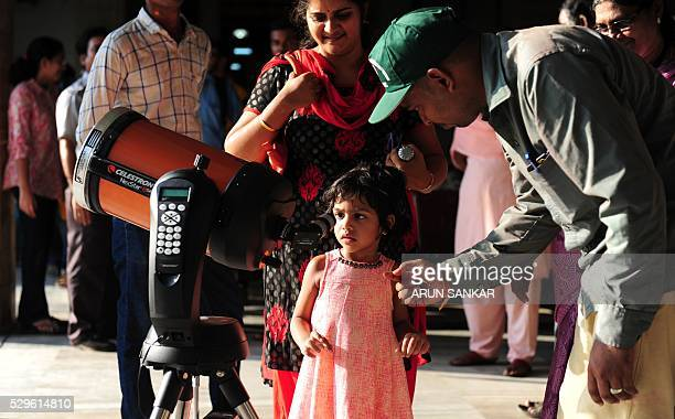 An Indian instructor helps a young child to watch images of Mercury's transit through a reflection from a telescope at The Birla Planetarium in...