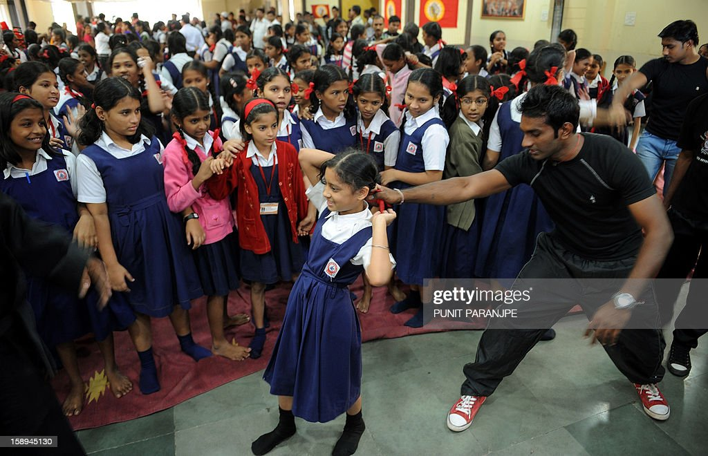 An Indian instructor (2R) shows a self defence technique to a school girl during a self-defence classes at a school in Mumbai on January 4, 2013. After nearly three weeks of lurid reporting on a horrifying gang-rape in New Delhi, women in the Indian capital say they are more anxious than ever, leading to a surge in interest in self-defence classes.