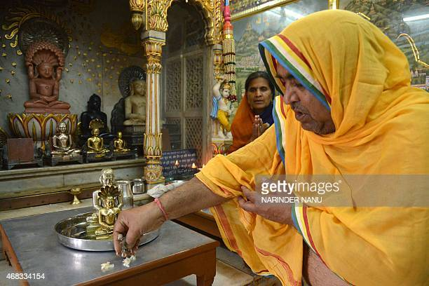 An Indian Jain priest is watched by devotees as he offers prayers to idols of Lord Mahavir on the occasion of Mahavir Jayanti at a temple in Amritsar...