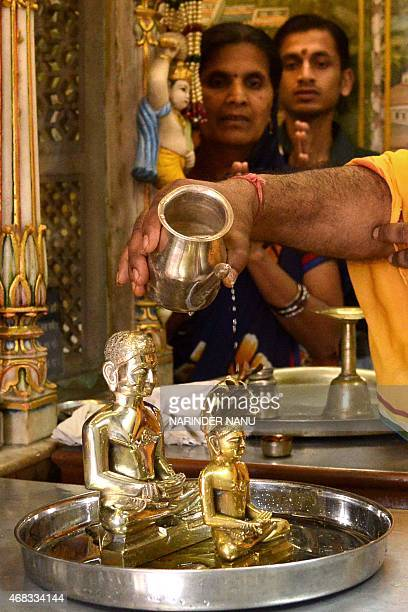 An Indian Jain priest is watched by devotees as he offers water to idols of Lord Mahavir on the occasion of Mahavir Jayanti at a temple in Amritsar...