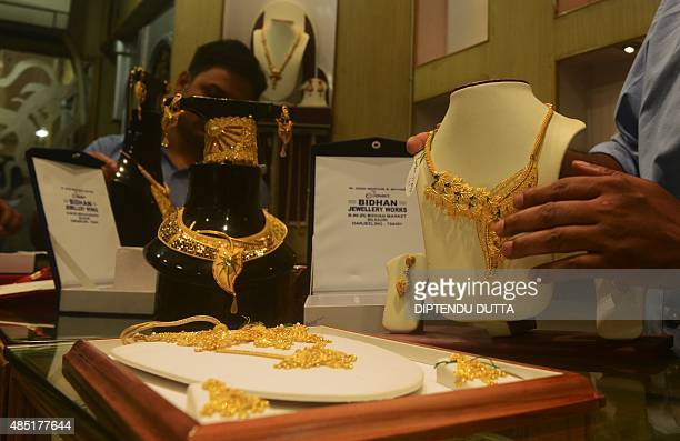 An Indian jewellery salesman adjusts gold items for sale at a store in Siliguri on August 25 2015 Prices of crude oil and most other commodities...