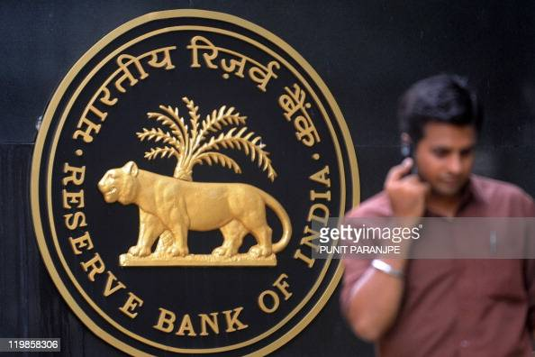 An Indian journalist speaks on a phone outside the head office of the Reserve Bank of India in Mumbai on July 26 2011 India's central bank on July 26...