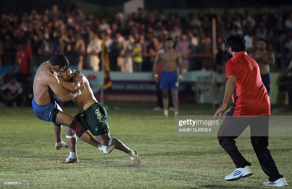An Indian kabaddi player (L) tries to tackle a Pakistani opponent during their final match of the 3rd Asian Kabaddi Circle Style Championship 2016 in Wah some 45 kilometers from Islamabad on May 6, 2016. / AFP / AAMIR