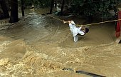 An Indian Kashmiri man crosses over flood waters with the use of a rope in Srinagar on September 9 2014 Bewildered families nursing children and...