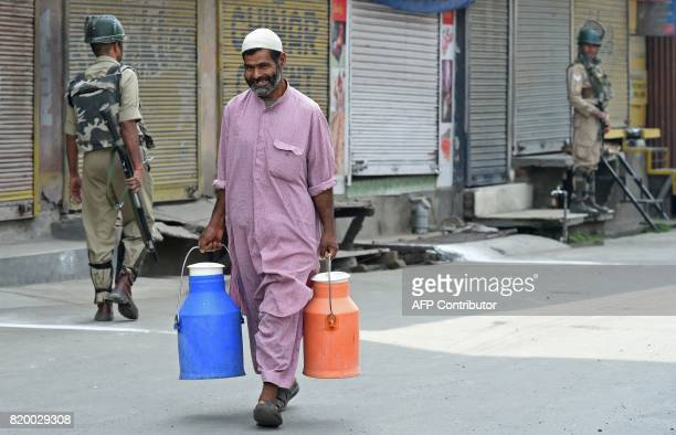 An Indian Kashmiri man smiles as he carries milk next to Indian paramilitary troopers standing guard in Srinagar on July 21 2017 Indian authorities...