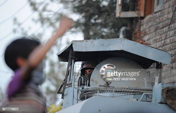 An Indian Kashmiri protestor shouts slogans as an Indian paramilitary trooper looks out from an armoured vehicle in Srinagar on November 8 2016 / AFP...