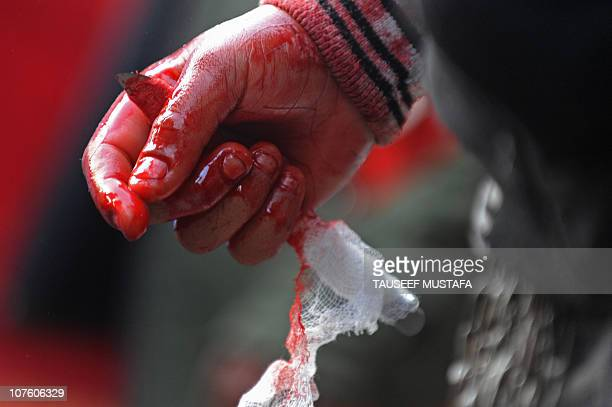 An Indian Kashmiri Shiite Muslim holds a knife to flagelate himself on December 14 2010 during a religious procession in Srinagar held on the seventh...