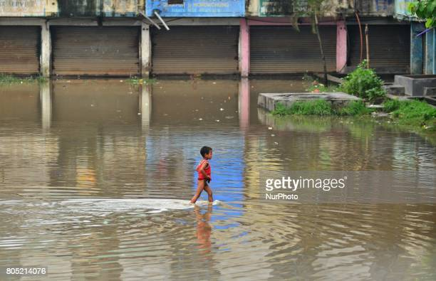 An Indian Kid walk passes flood water in a residential area after a heavy rainfall in Dimapur India north eastern state of Nagaland on Saturday 01...