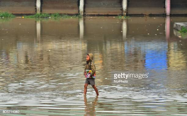 An Indian Kid with books in his hand walk passes flood water in a residential area after a heavy rainfall in Dimapur India north eastern state of...