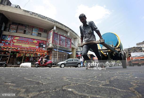 An indian laborer pulls a water tank at a hot day in Mumbai on May 29 2015 At least 1400 people have died in a major heatwave that has swept across...