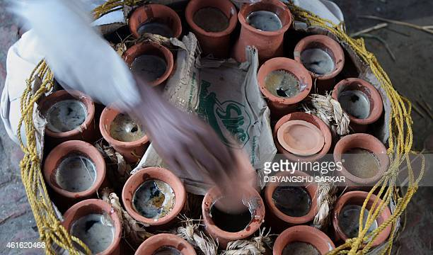 An Indian labourer arranges mudpots filled with jaggery cane sugar made from the date palm tree for sale at the market in Joynagar around 50 kms...