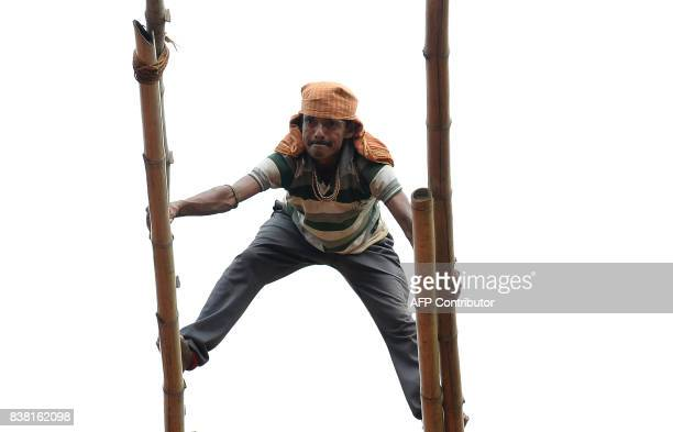 An Indian labourer balances on bamboo poles as he erects a temporary shelter for an event in New Delhi on August 24 2017 / AFP PHOTO / SAJJAD HUSSAIN