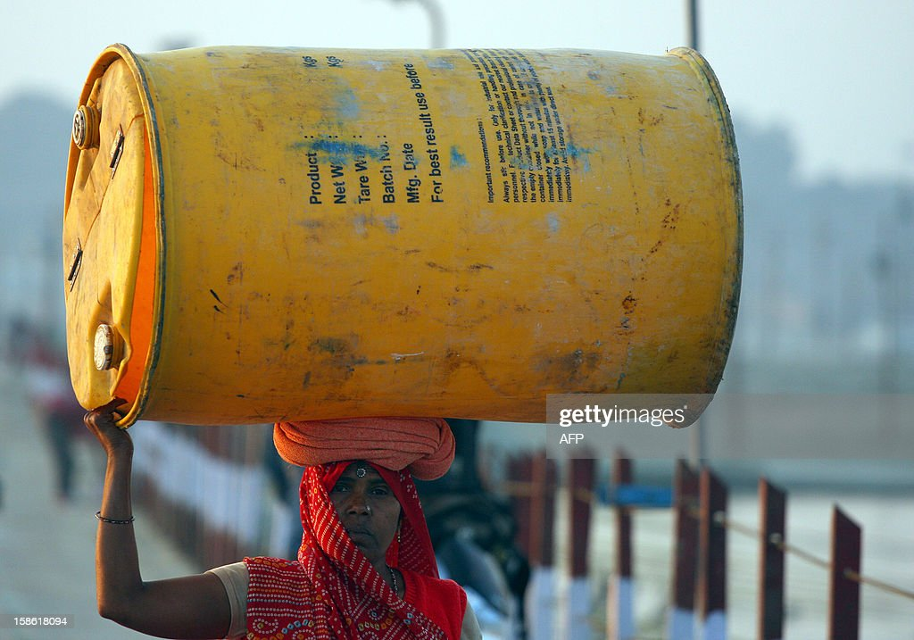 An Indian labourer carries a plastic drum on her head as she walks close to the site of The Kumbh Mela in Allahabad on December 21, 2012. The Kumbh Mela, which is scheduled to take place in the northern Indian city in January and February 2013, is the world's largest gathering of people for a religious purpose and millions of people gather for this auspicious occasion. AFP PHOTO/ Sanjay KANOJIA