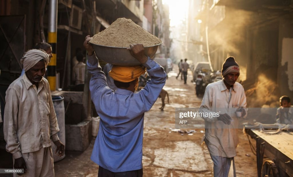 An Indian labourer carries sand near a construction site, as other labours drink tea in New Delhi on March 17, 2013. Indian business leaders and the government have for months been calling for lower lending rates to help the once-booming economy, forecast to see a five percent growth rate in the year to March 2013, the weakest in a decade. AFP PHOTO/ Andrew Caballero-Reynolds