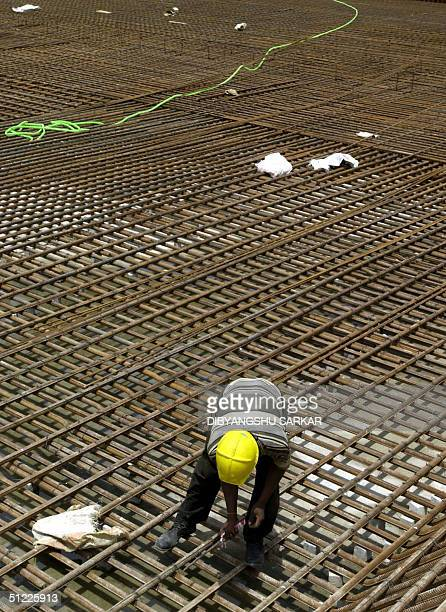 An Indian labourer examines a joint in a set of iron rods at a construction for a Prototype Fast Breeder Reactor at the Indira Gandhi Centre for...