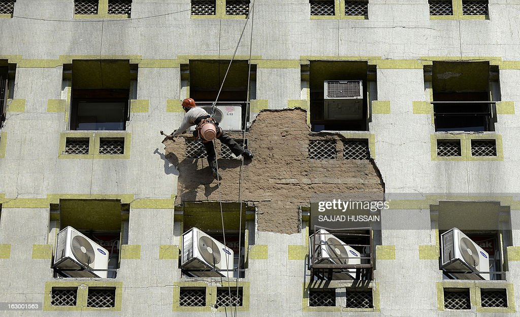 An Indian labourer hangs from a rope as he hammers cement plaster from the wall of a building in New Delhi on March 3, 2013. India's finance minister P. Chidambaram pledged in his budget to cut a gaping fiscal deficit in a bid to avert a damaging credit ratings downgrade, but economists remain sceptical he can meet his goal.