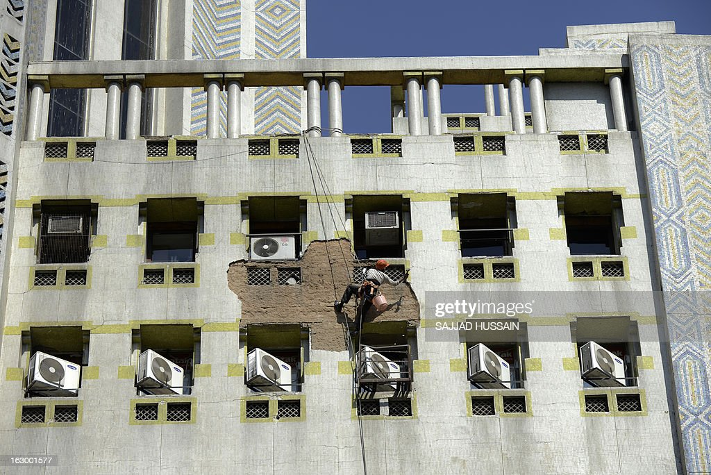 An Indian labourer hangs from a rope as he hammers cement plaster from the wall of a building in New Delhi on March 3, 2013. India's finance minister P. Chidambaram pledged in his budget to cut a gaping fiscal deficit in a bid to avert a damaging credit ratings downgrade, but economists remain sceptical he can meet his goal. AFP PHOTO/ SAJJAD HUSSAIN