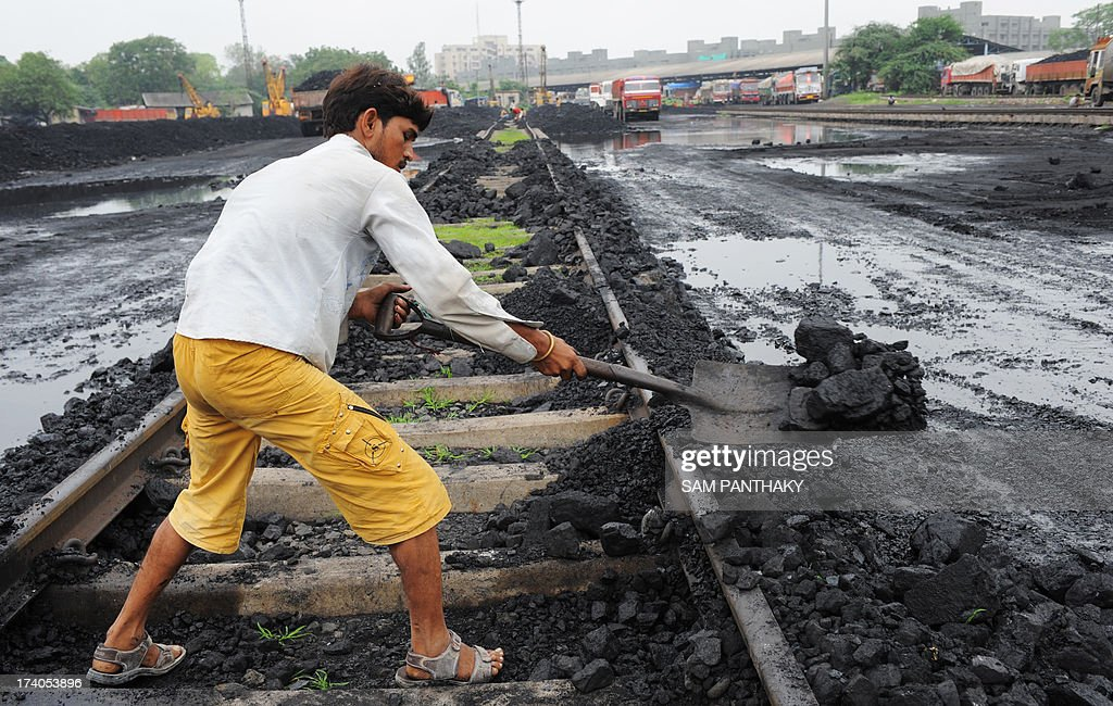 An Indian labourer lifts coal from a railway track to be transported to a truck at the Kankaria Railway yard in Ahmedabad on July 20, 2013. In 1973, India nationalised its coal industry and created state-run giant Coal India. Then in 1993 it allowed private companies to mine coal for their own use when state output could not supply demand. AFP PHOTO/ Sam PANTHAKY