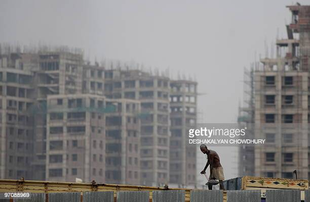 An Indian labourer offloads sand from a truck at a construction site at 'New Town' on the outskirts of Kolkata on February 26 2010 India's economic...