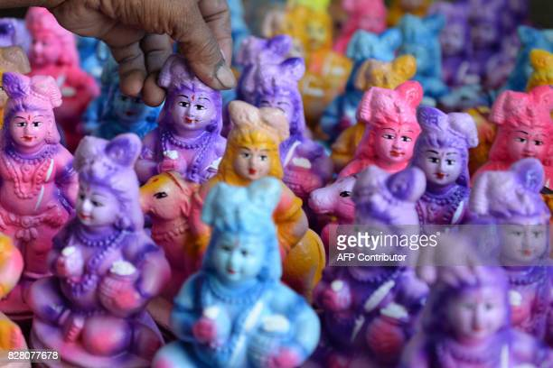 An Indian labourer paints statues of the Hindu god Lord Krishna at a workshop during the forthcoming Krishna Janmashtami in Chennai on August 9 2017...