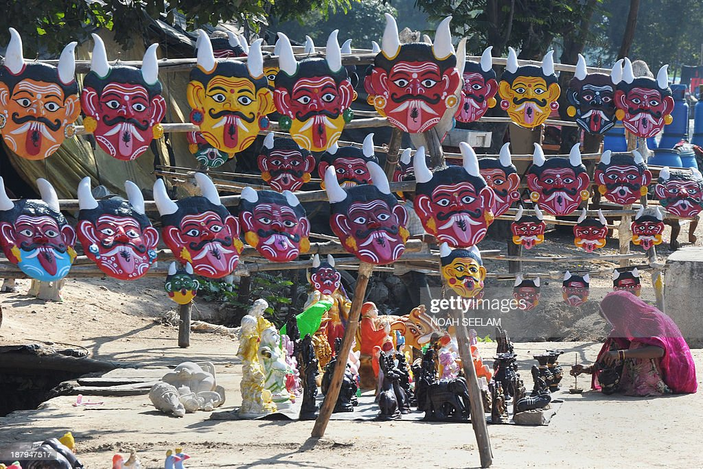 An Indian labourer paints statuettes for sale at a stall selling masks depicting the devil, and believed to ward off evil if hung outside homes, outside a makeshift shelter on a highway on the outskirts of Hyderabad on November 14, 2013. India's inflation increased to 7.0 percent last month, providing further evidence that the country is battling the twin problems of rising prices and slowing economic growth. AFP PHOTO / Noah SEELAM