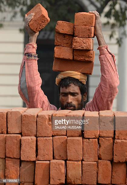 An Indian labourer places bricks on his head at a construction site in New Delhi on January 12 2014 India's industrial output shrank by an unexpected...