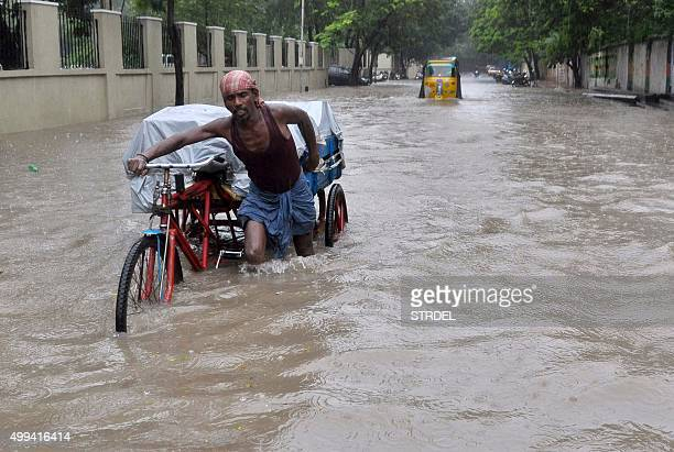 An Indian labourer pushes his cycle trishaw through floodwaters in Chennai on December 1 during a downpour of heavy rain in the southern Indian city...